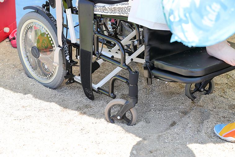 【写真】車椅子のタイヤが砂浜にめり込んでしまっている