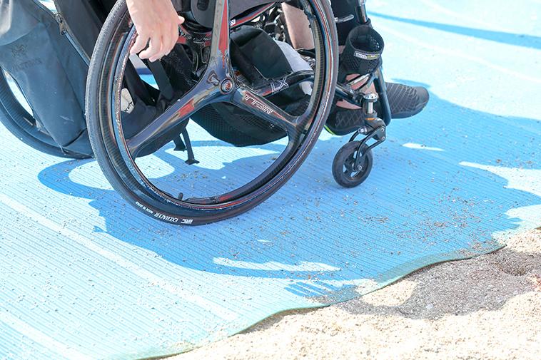 【写真】ビーチマットを敷いて車椅子を走らせた時の様子。タイヤが一切めり込んでいない