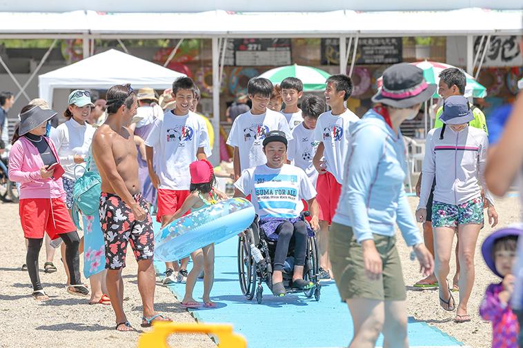 【写真】老若男女に囲まれながら笑顔でビーチマットの上を進む車椅子の男性