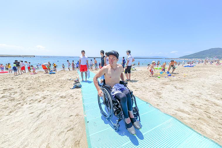 【写真】砂浜に敷いたビーチマットの上を車椅子で進むきどさん