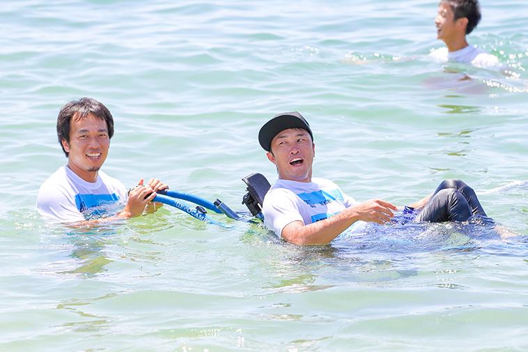【写真】男性に支えられ、車椅子に乗ったまま海に入るきどさん