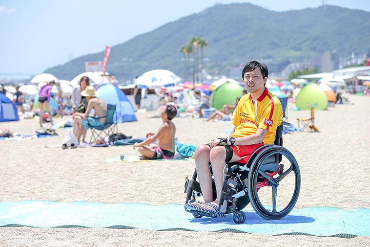 【写真】ライフセーバーの服を着て、ビーチマットの上で車椅子に乗るふるなかさん