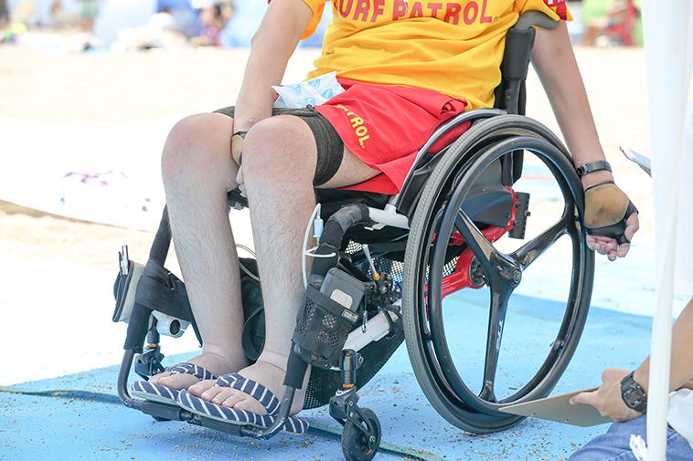 【写真】ビーチマットの上を車椅子で進むふるなかさん