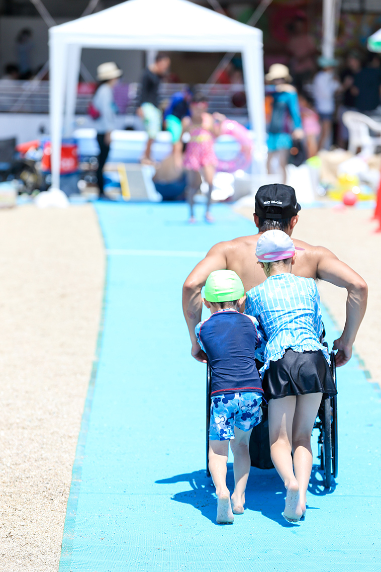 【写真】ビーチマットの上を車椅子で進む男性と、それを後ろから押す子どもたちの後ろ姿