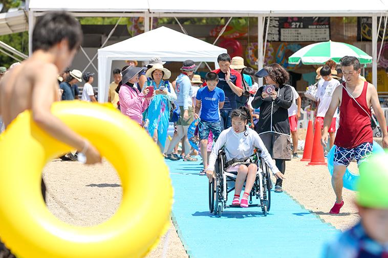 【写真】車椅子に乗った女の子が、砂浜の上に敷かれたビーチマットの上を進んでいく