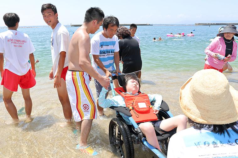 【写真】男性らに支えられながら、車椅子で海に入る女の子