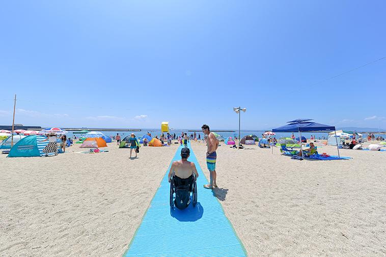 【写真】海に向かってまっすぐ繋がっている砂浜の上のビーチマットを、車椅子に乗った男性が進んでいく