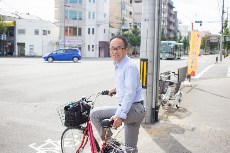 【写真】街頭で笑顔で自転車に乗っているきもとつとむさん