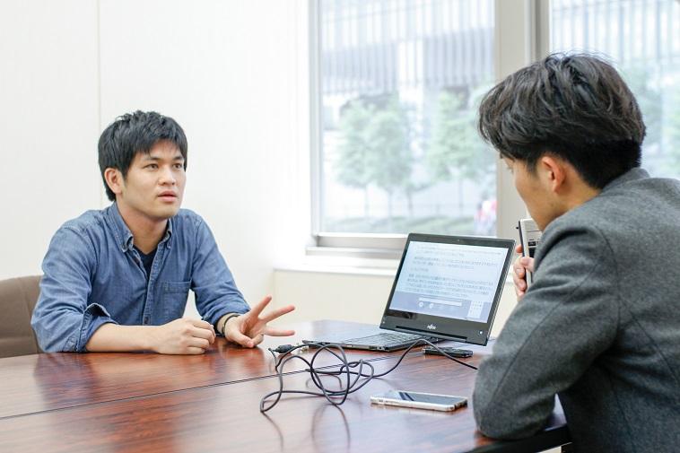 【写真】インタビューに真剣に応えてくれるまつだよしきさんとLiveTalkを口元に持っているライターのすずきゆうへい