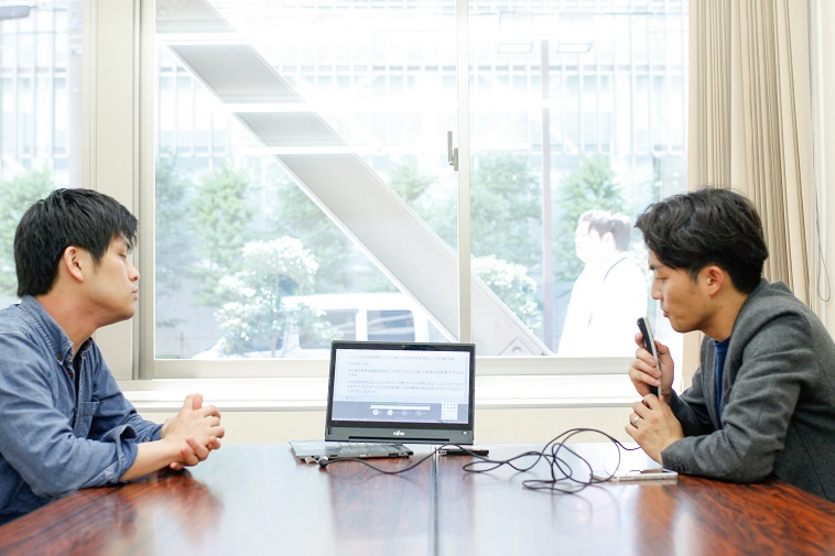 【写真】LiveTalkを使ってインタビューをするライターのすずきゆうへいと、文字起こしが表示されているパソコンを見るまつだよしきさん