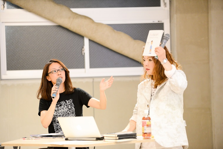 【写真】ぷるすあるはのお2人。作品を掲げながら活動について説明している