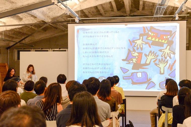 【写真】ぷるすあるはの絵本がスライドで紹介されている