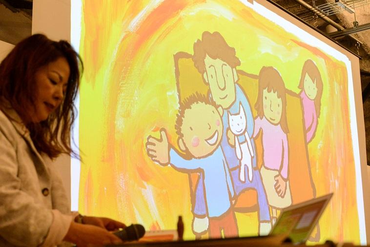 【写真】スライド全体に映し出された、ぷるすあるはのイラスト。温かみのある家族の絵が描かれている
