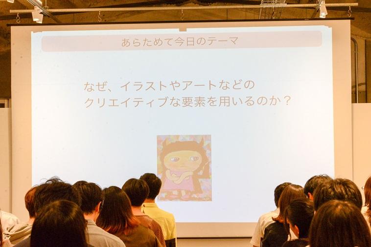 【写真】「なぜ、イラストやアートなどのクリエイティブな要素を用いるのか?」と書かれたスライドが写し出されている
