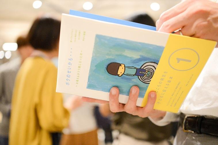 【写真】ぷるすあるはの絵本を手に取る参加者
