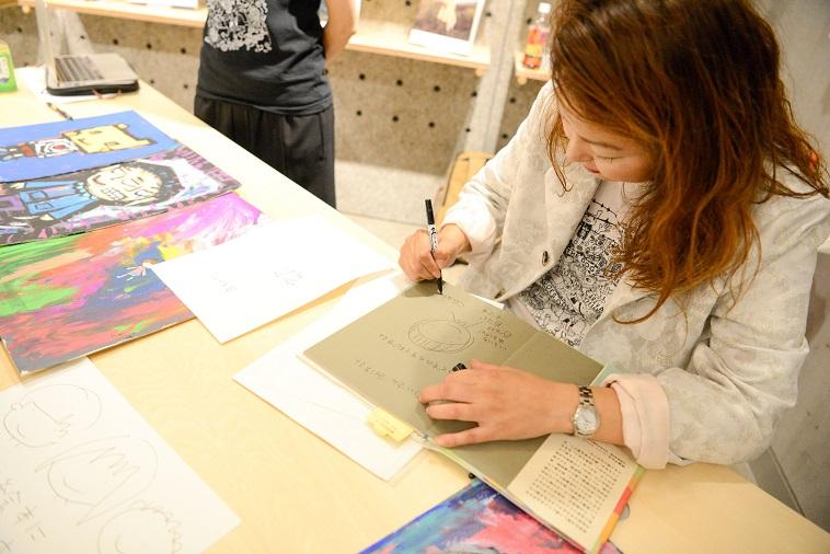 【写真】絵本にサインをするちあきさん