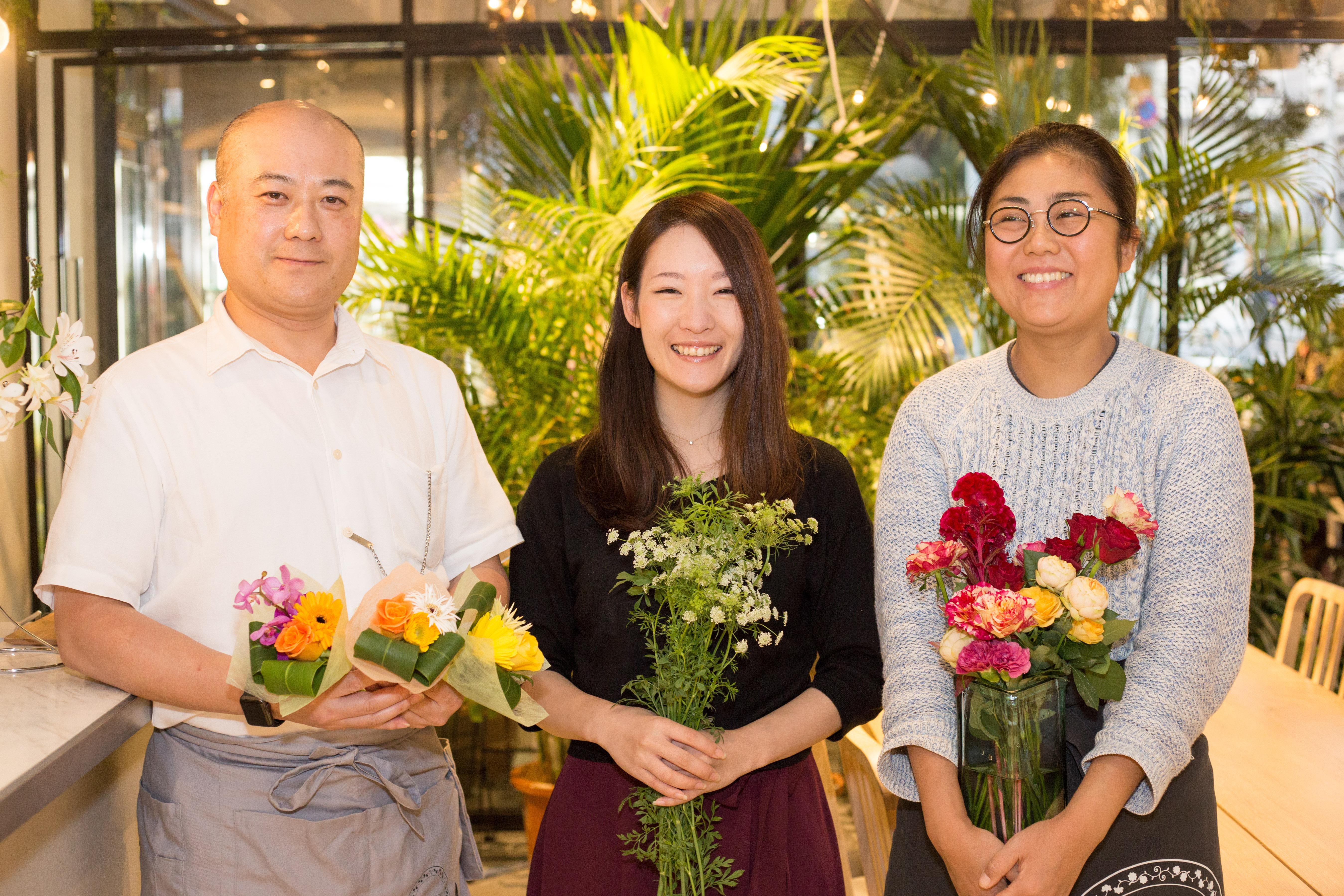 【写真】様々な種類のお花を手に持ち、笑顔を向けるローランズスタッフ3人