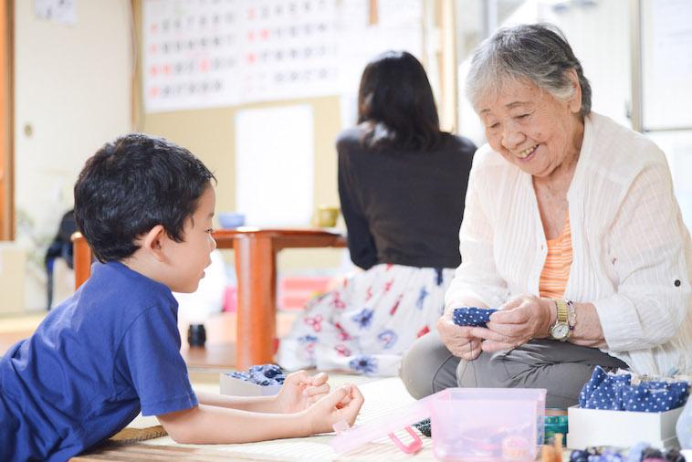 【写真】針仕事をするおばあちゃんと、それを見つめる小さな男の子。