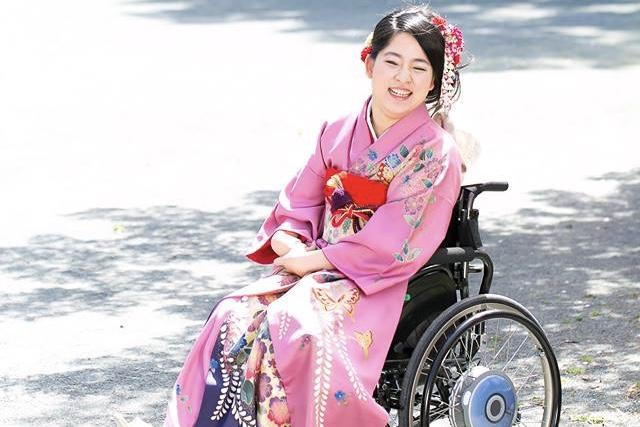 【写真】車椅子に座り、振袖を身につけて笑顔で写る女性。嬉しさが伝わってくる。