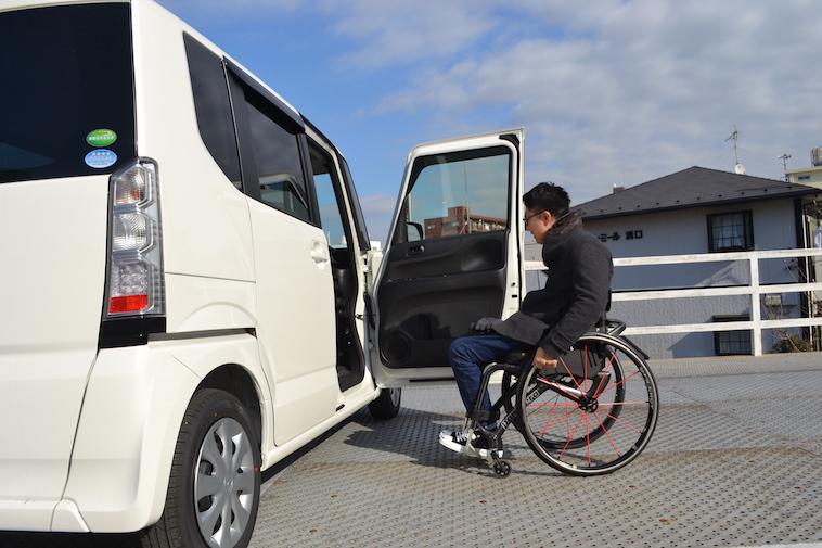 【写真】車椅子で車に乗り込もうとするかみむらさん