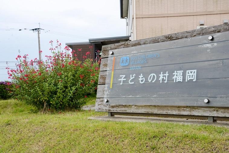 【写真】「子どもの村福岡」の看板。横には植物が生えている