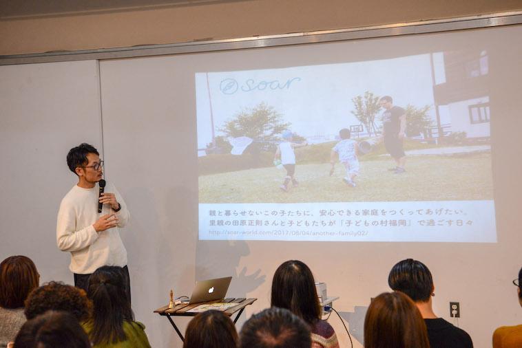 【写真】子どもの村の写真をスライドで示しながら話すたきたさん