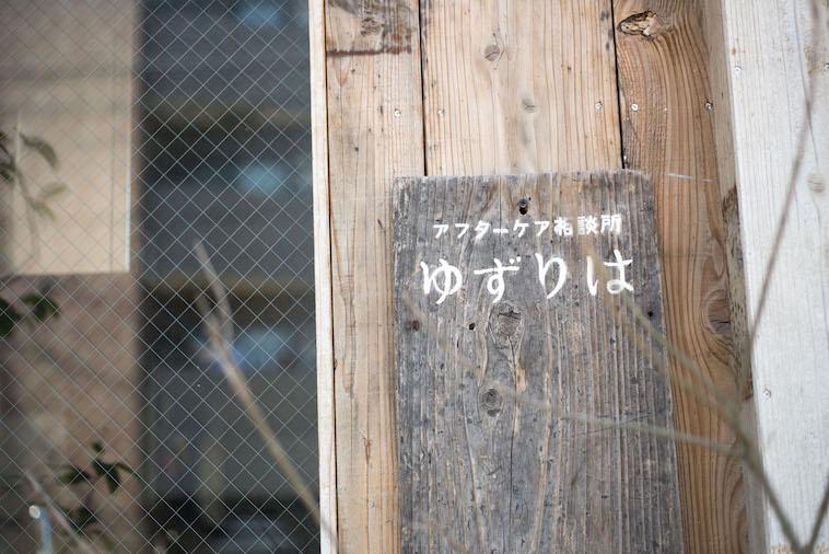【写真】木の看板に書かれた「アフターケア相談所ゆずりは」の文字