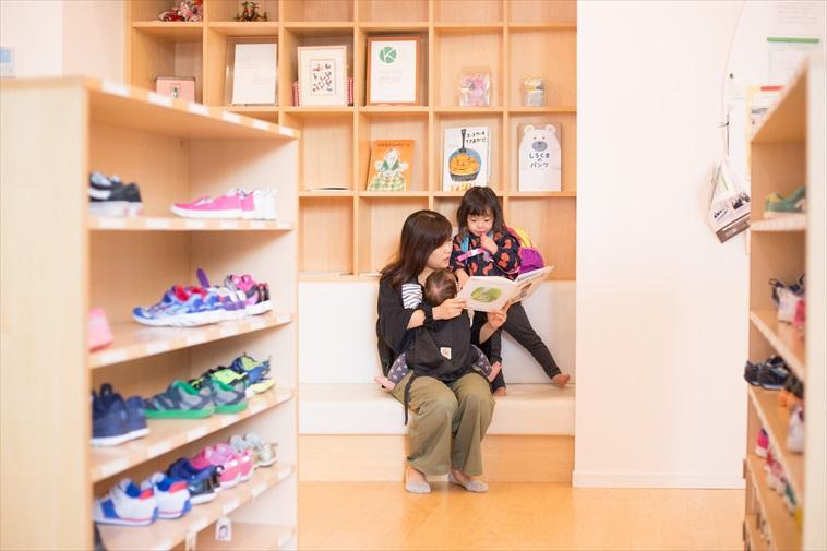 保育園のソファで読み聞かせをするお母さんと真剣に聞く子ども