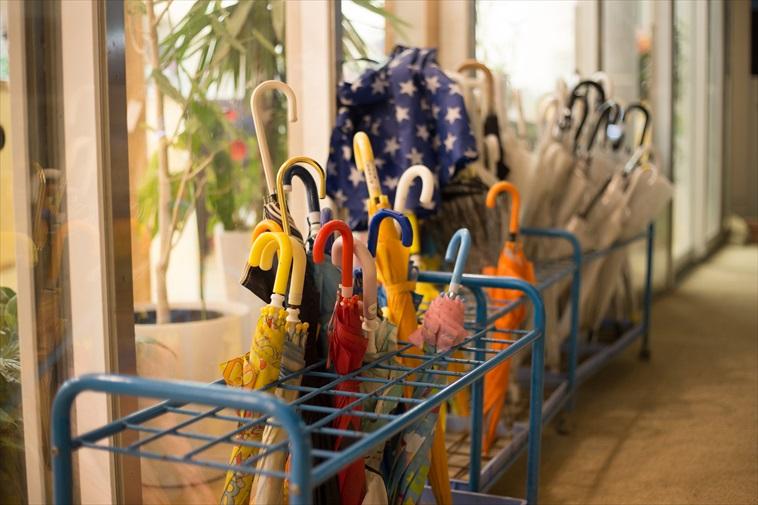 【写真】どろんこ保育園の傘立てにはたくさんの傘が立てかけられている。