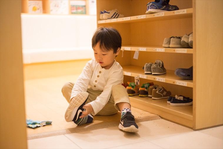 【写真】玄関に座り少しずつ自分で靴を履こうとする子ども
