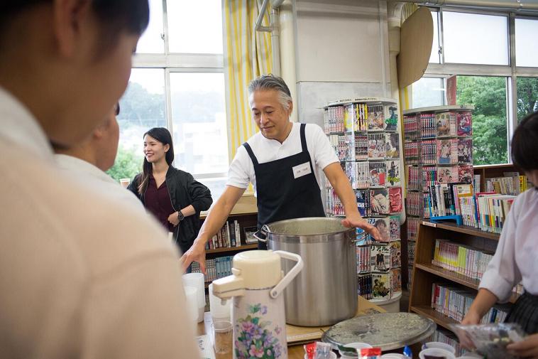 【写真】ボランティアさんが生徒にスープをついで渡している