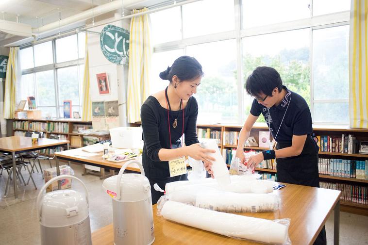【写真】プラスチックコップを空けてカフェの準備をしているスタッフたち