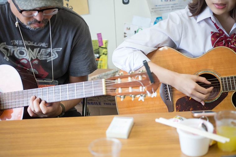 【写真】並んで座ってギターを合わせるいしいまさひろさんと女子生徒