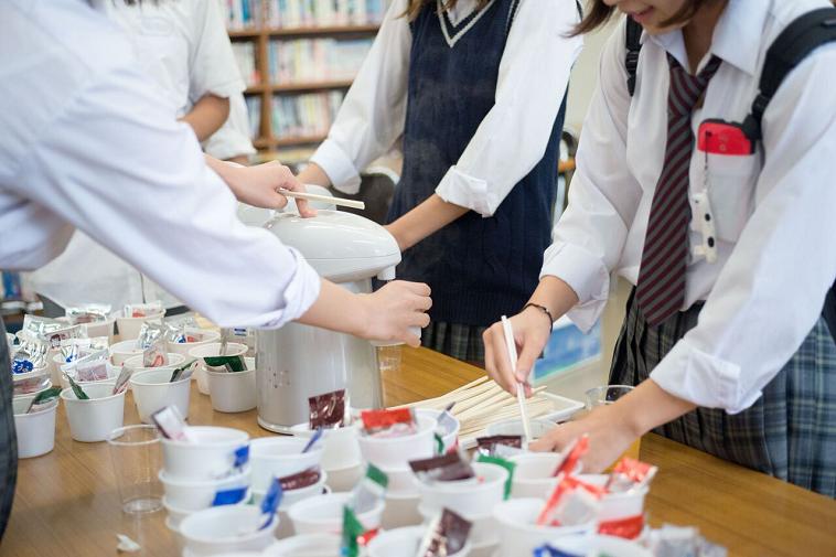 【写真】インスタント味噌汁にお湯を入れる学生