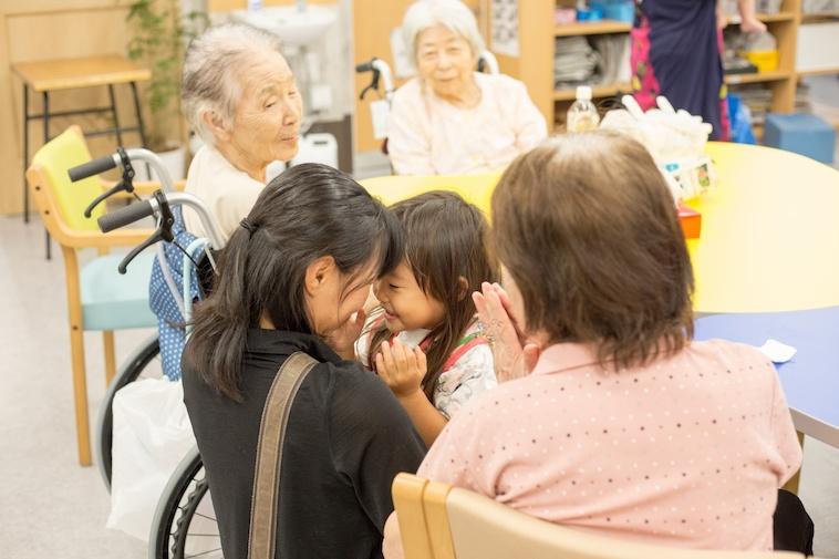【写真】子どもとお母さんをにこやかに見守るおばあちゃんたち