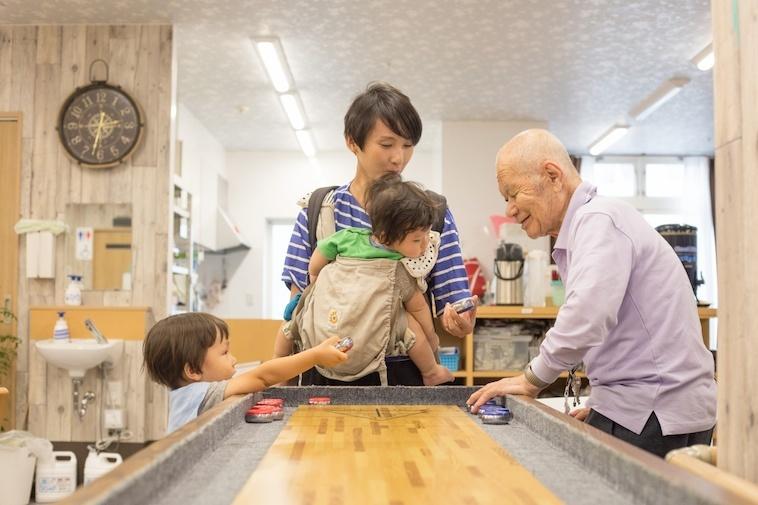 【写真】子どもとお母さんに遊びを教えるおじいちゃん
