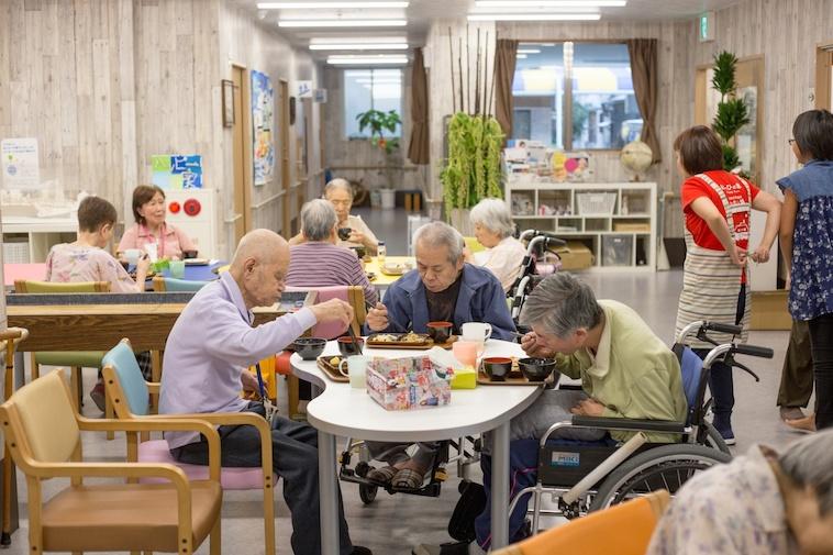 【写真】一つの机を囲みお昼ご飯をたべるおじいちゃんたち