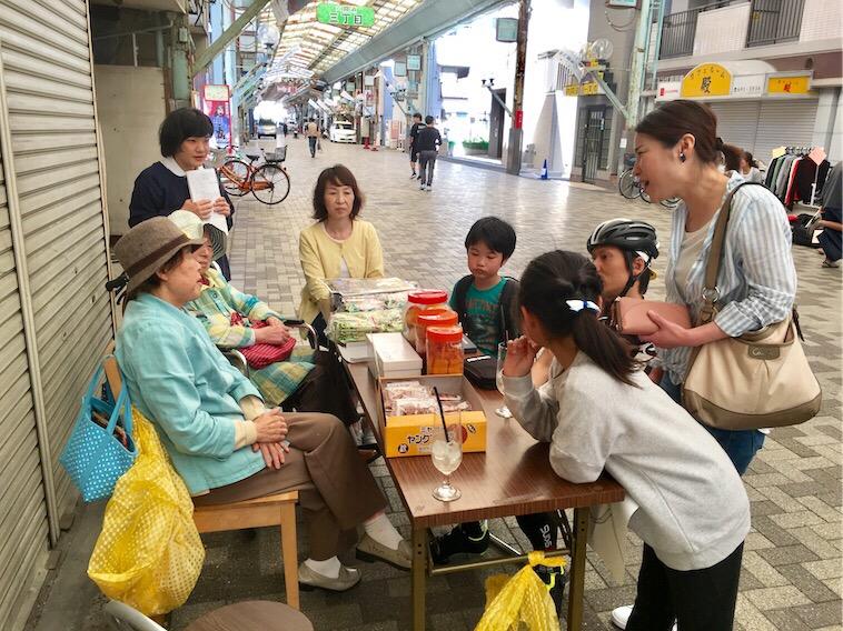 【写真】おばあちゃんがろっけんどう商店街で子連れのおかあさんの人生相談にのる様子