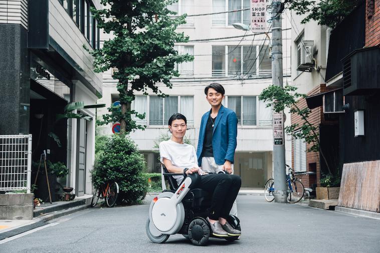 【写真】街頭で車椅子に座っている笑顔のむとうまさたねさんとライターのすずきゆうへい
