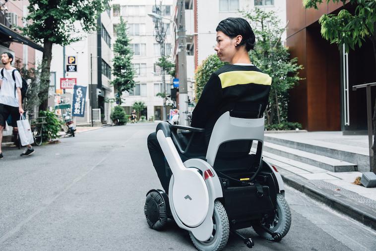 【写真】街頭で車椅子に座り移動をするむとうまさたねさん