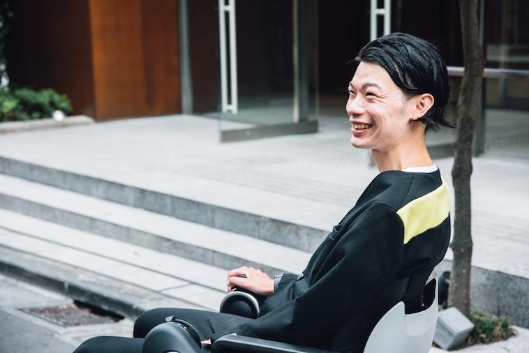 【写真】街頭で車椅子に座って笑顔のむとうまさたねさん