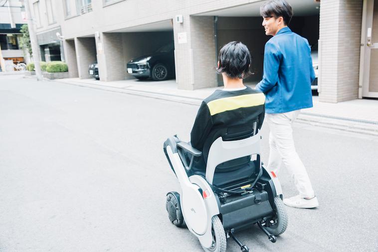 【写真】街頭で車椅子に座って移動するむとうまさたねさんとライターのすずきゆうへい