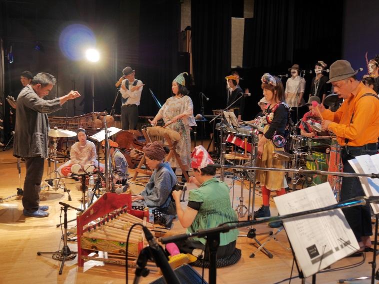 【写真】舞台の上で指揮者を中心に集まる演奏者たち。それぞれが自分なりの表現を行なっている。
