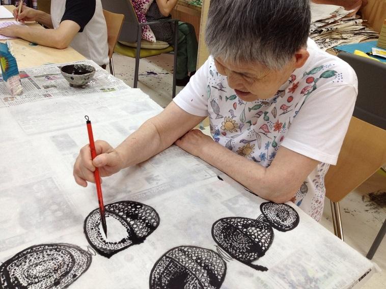 【写真】白地の布に筆で絵を描いていく利用者。緻密に描かれた絵に思わず見入ってしまう。