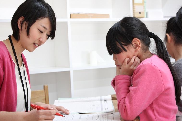 【写真】勉強を教えるスタッフと、真剣な眼差しで学ぶ子ども。