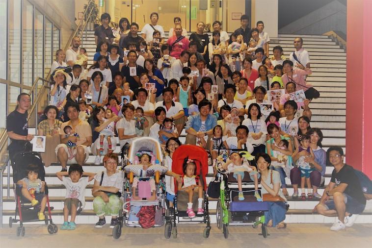 【写真】建物の階段で、チーム18に参加しているたくさんの家族の集合写真を撮影した様子