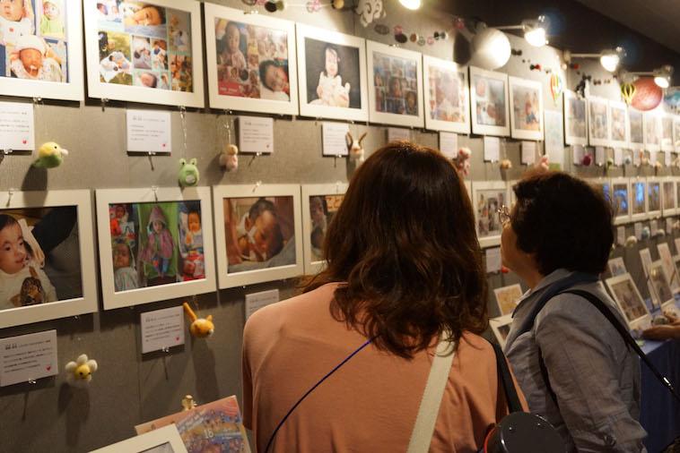 【写真】チーム18が開催した写真展で、熱心に写真を見る来場者の女性2人