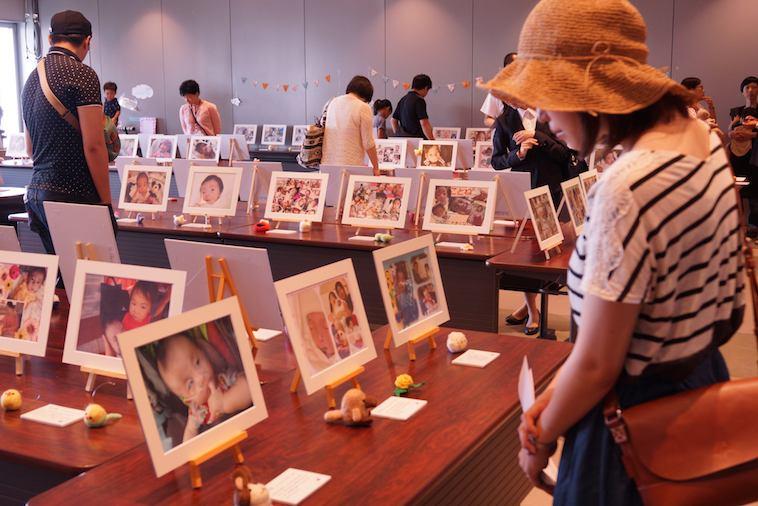 【写真】机に並べられた子どもたちの写真を見入る来場者の女性