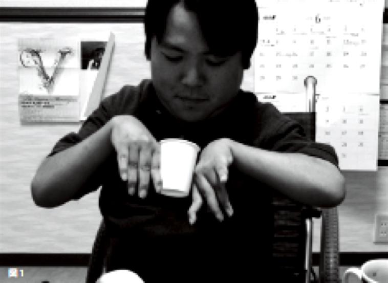 【写真】くまがやさんが、手の甲を使ってコップを持ち上げる様子