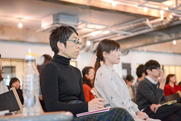 【写真】ノートを膝に置き、登壇者の話を聞く参加者ら